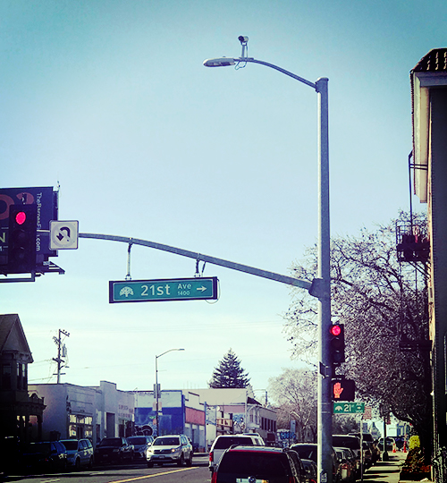 Street sign says 21st Ave. There's a CCTV camera above.
